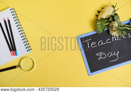 Asters Flowers Lying Down On A Chalkboard With Text Teachers Day , And A Magnifier Loupe Next To Col