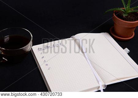 Opened Agenda, Notepad, Organizer With List To Do On Blank White Sheets, Cup Of Coffee And Potted Su