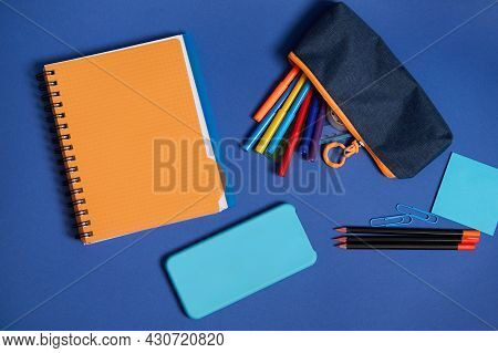 Top View Of School Office Supplies And A Smartphone Lying Screen Down On A Blue Background . Flat La