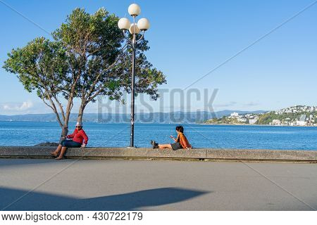 Wellington New Zealand - July 30 2021; Two Urban Women Using Device While Relaxing At Waters Edge On