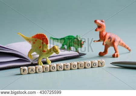 Paleontology Inscription Next To Toy Dinosaurs And An Open Notebook. Concept For Studying Cryptozool