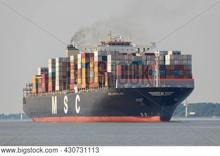 Stade, Germany - June 25, 2021: Container ship MSC REGULUS, built by Hyundai Heavy Industries, currently chartered to Mediterranean Shipping Company (MSC) on Elbe river.
