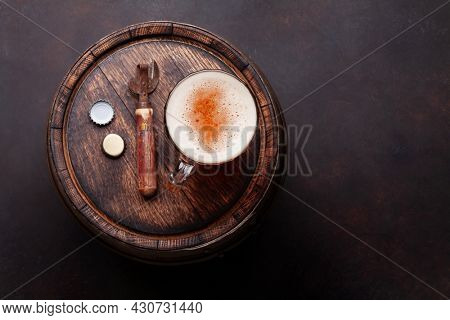 Lager beer mug on old wooden barrel. Top view flat lay with copy space