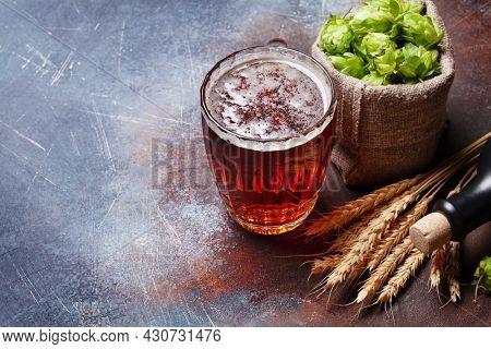 Lager beer mug, hops and wheat on old stone table. With copy space