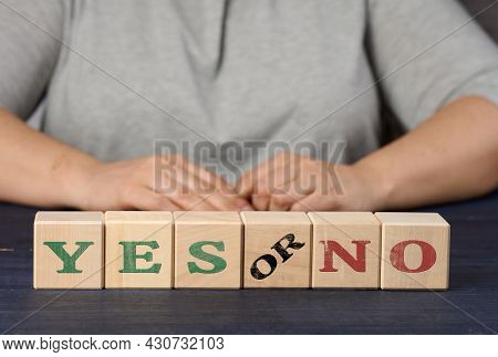 Wooden Cubes With The Inscription Yes And No On A Nlue Background. The Concept Of Analyzing And Choo
