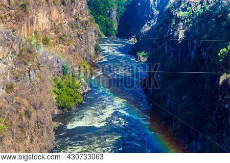 Gorgeous rainbow. Ropes for canopy stretched over a canyon with a raging  african Zambezi River. The waterfall Victoria Falls on the Zambezi River. Concept of extreme and photo tourism