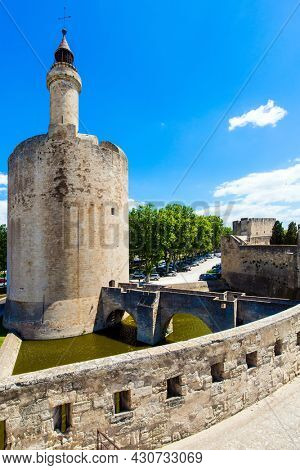 The historic round tower of Constance. Powerful medieval walls and a moat with water surround the ancient city of Aigues-Mortes. Mediterranean coast of France. The concept of historical tourism