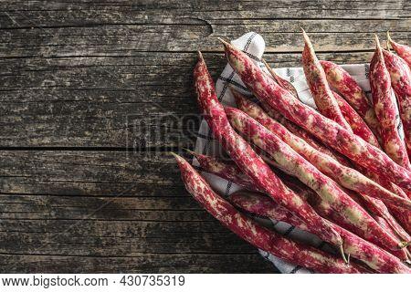 Cranberry beans. Borlotti beans. Beans pods on wooden table. Top view.