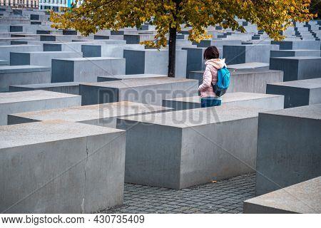 Berlin, Germany - 20 September 2019: Woman standing between stelae of Holocaust Memorial in Berlin, Germany