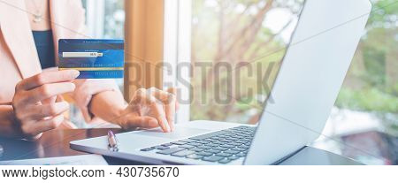 Woman Paying Online Bills With Credit Card.she Uses A Laptop Computer To Search Online.