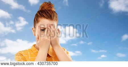 fear, vision and shame concept - scared, shy or embarrassed red haired teenage girl closing one eye by hand and looking through fingers over clouds in blue sky background