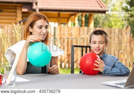 A Boy With His Mother Inflates Two Colorful Balloons On A Warm Summer Day In The Garden. Birthday Pr