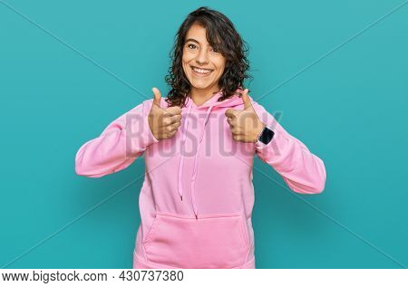 Young hispanic woman wearing casual sweatshirt success sign doing positive gesture with hand, thumbs up smiling and happy. cheerful expression and winner gesture.