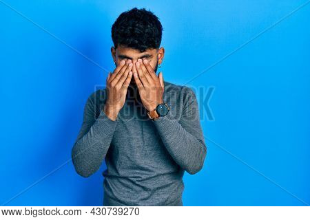 Arab man with beard wearing turtleneck sweater rubbing eyes for fatigue and headache, sleepy and tired expression. vision problem