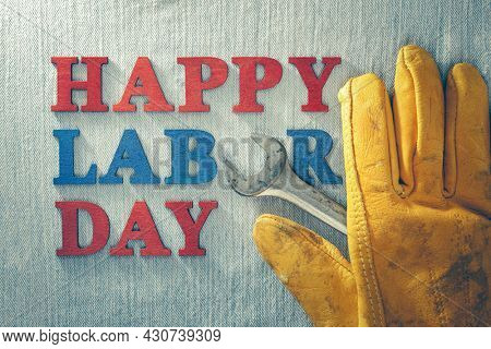 Worn and weathered work glove and wrench with Happy Labor Day text, celebrating American workers.