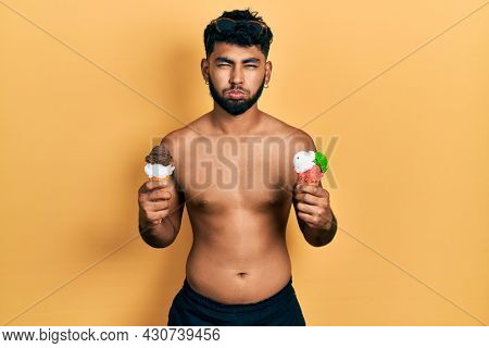 Arab man with beard wearing swimwear eating two ice cream cones puffing cheeks with funny face. mouth inflated with air, catching air.