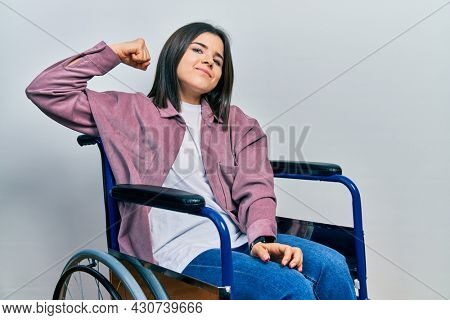 Young brunette woman sitting on wheelchair strong person showing arm muscle, confident and proud of power