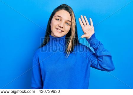 Young brunette girl wearing turtleneck sweater waiving saying hello happy and smiling, friendly welcome gesture