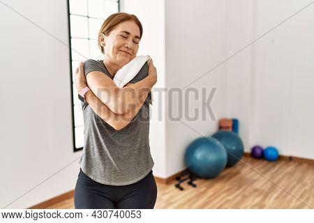 Middle age woman wearing sporty look training at the gym room hugging oneself happy and positive, smiling confident. self love and self care