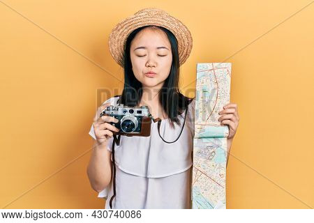 Young chinese girl holding city map and vintage camera looking at the camera blowing a kiss being lovely and sexy. love expression.