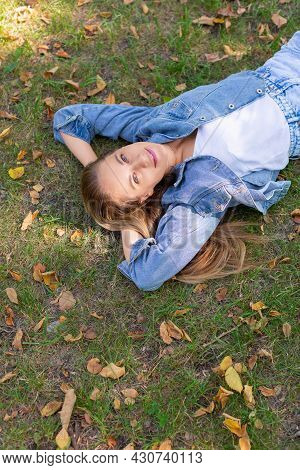 Digital Detox Concept - Pensive Young Woman Lies In The Park On The Grass.