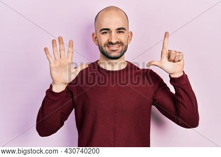 Young bald man wearing casual clothes showing and pointing up with fingers number seven while smiling confident and happy.