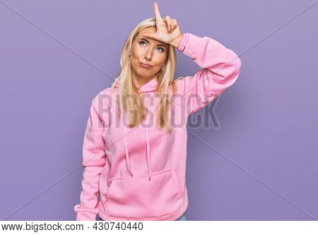 Young blonde woman wearing casual sweatshirt making fun of people with fingers on forehead doing loser gesture mocking and insulting.