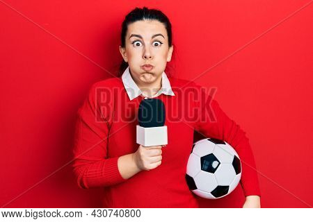 Young hispanic woman holding reporter microphone and soccer ball puffing cheeks with funny face. mouth inflated with air, catching air.