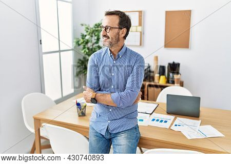 Middle age hispanic man with beard wearing business clothes at the office smiling looking to the side and staring away thinking.