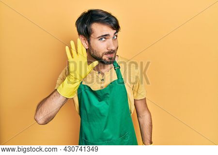 Young hispanic man wearing cleaner apron and gloves smiling with hand over ear listening and hearing to rumor or gossip. deafness concept.
