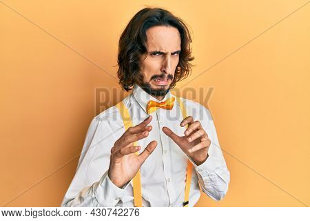 Young hispanic man wearing hipster elegant look disgusted expression, displeased and fearful doing disgust face because aversion reaction. with hands raised