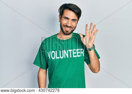 Young hispanic man wearing volunteer t shirt waiving saying hello happy and smiling, friendly welcome gesture
