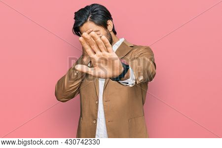 Young hispanic man wearing business clothes covering eyes with hands and doing stop gesture with sad and fear expression. embarrassed and negative concept.
