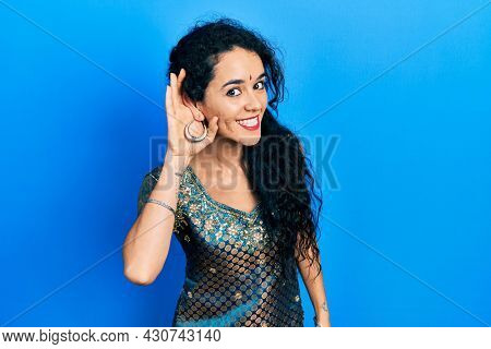 Young woman wearing bindi and traditional kurta dress smiling with hand over ear listening an hearing to rumor or gossip. deafness concept.