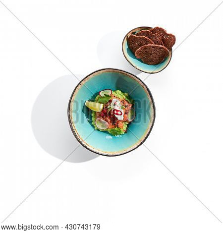 Salmon tartare close up. Raw red fish with seasoning and crackers in plate. Served chopped fresh tuna with bread slices. Seafood restaurant food with herbs decoration. Marine delicacy, gourmet meal