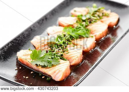 Salmon tataki - seared salmon, thinly sliced sashimi style. Salmon tataki served with delicious citrus ponzu tataki sauce and fresh greens. Japanese seafood on black plate isolated on white background