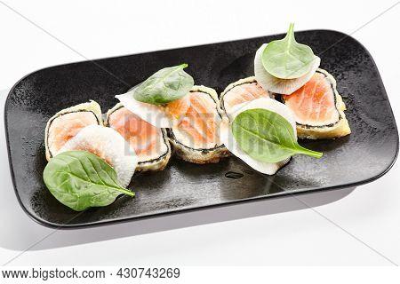 Salmon tataki - seared salmon. thinly sliced sashimi style. Salmon tataki served with delicious citrus ponzu tataki sauce. Japanese seafood on black plate isolated on white background