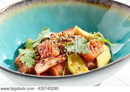 Salmon and avocado salad bowl. Blue salad bowl isolated on white background. Salad garnished with micro greens and sesame, chopped salmon, sliced avocado and parsley green leaf. Salmon and spicy sauce