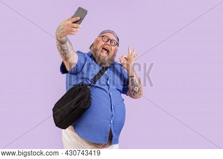 Plump Hipster Shows Ok Gesture Taking Selfie With Mobile Phone On Purple Background