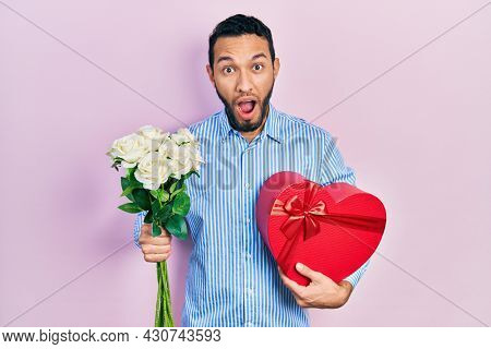 Hispanic man with beard holding anniversary present and bouquet of flowers afraid and shocked with surprise and amazed expression, fear and excited face.