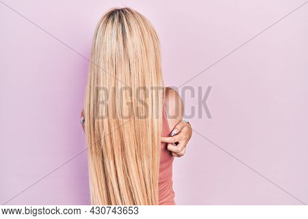 Young blonde girl wearing casual clothes hugging oneself happy and positive from backwards. self love and self care