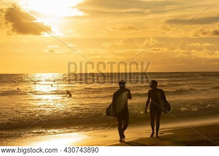 Couple of surfers leaving the water after surfing on a beautiful golden sunset at the beach. Body board and surf lifestyle concept.