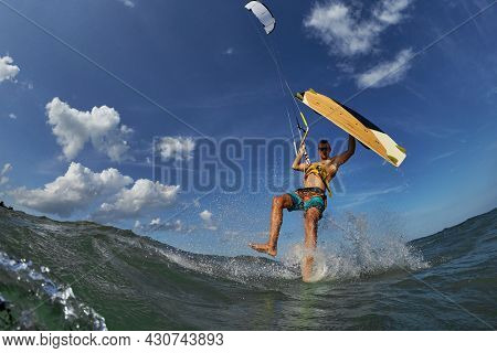Kite surfer jumps with kiteboard in transition