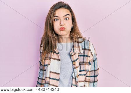 Young caucasian girl wearing casual clothes puffing cheeks with funny face. mouth inflated with air, crazy expression.