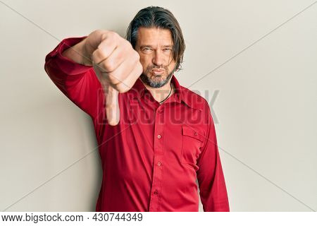 Middle age handsome man wearing casual clothes looking unhappy and angry showing rejection and negative with thumbs down gesture. bad expression.
