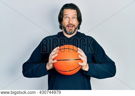Middle age caucasian man holding basketball ball afraid and shocked with surprise and amazed expression, fear and excited face.