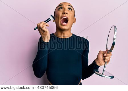 Hispanic man wearing make up and long hair holding mirror applying make up angry and mad screaming frustrated and furious, shouting with anger looking up.