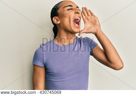 Hispanic man wearing make up and long hair wearing casual t shirt shouting and screaming loud to side with hand on mouth. communication concept.
