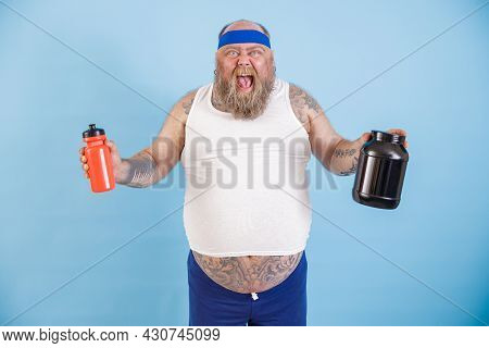 Excited Plump Man With Headband Holds Bottles Of Drink And Protein Supplement In Studio
