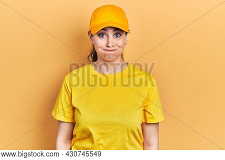 Young hispanic woman wearing delivery uniform and cap puffing cheeks with funny face. mouth inflated with air, crazy expression.